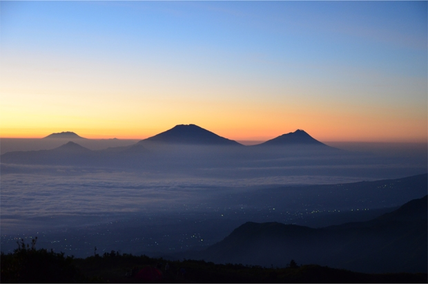 The dormant volcano Merbabu (left) and its active neighbor Merapi, as seen from Mt. Prahu
