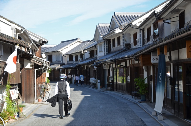 Small restaurants, cafes, and stores line a main road in Honmachi